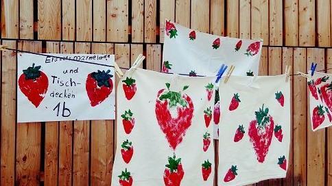 Selbstgemachte Erdbeermarmelade aus handverlesenen Erdbeeren vom Erdbeerfeld wurde neben bedruckten Tischdecken angeboten.